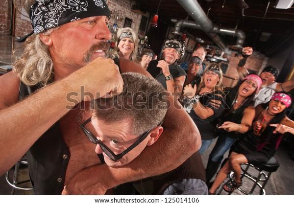 Bearded gang member holding nerd in a head lock