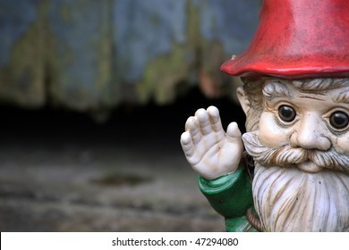 A bearded garden gnome on a landscape format set to the right of the image waving his hand. Set against a wooden garden shed door.