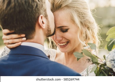 Bearded groom kisses bride's forehead while she cries