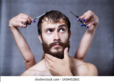 Bearded guy in the barber shop. In the background are the hands of a girl. Gray background.