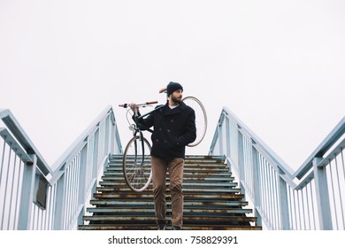 Bearded guy carrying bicycle on shoulders