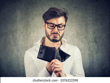 Bearded guy in glasses being broke having holes in wallet instead of money.