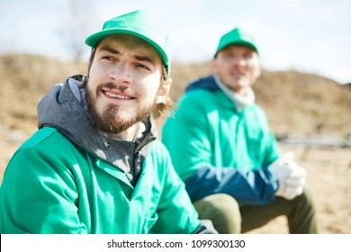 Bearded guy in green uniform and his colleague having rest after work in natural environment