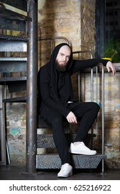 A bearded guy on the stairs. Bearded bald hipster in white sneakers
