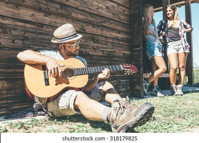 bearded guy playing guitar in mountains near wooden house