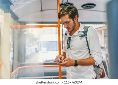 Bearded  guy is reading emails on a display of a smartphone connected to public wi-fi while sitting in a city bus. Handsome male is looking at the screen of a mobile phone while texting.