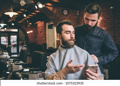 Bearded guy is showing to hairdresser a picture on the phone. Hairdresser is looking at the phone with serious sight.
