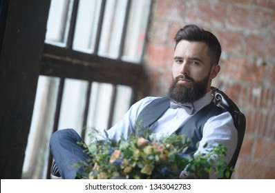 Bearded guy sitting holding flowers