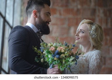 Bearded guy in a suit holding flowers and a bride