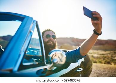 bearded guy in vintage car taking selfie