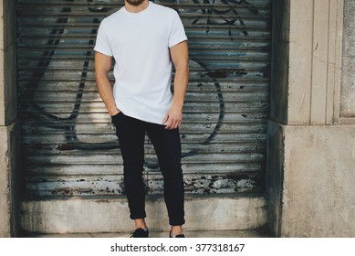 Bearded guy wearing white blank t-shirt and black jeans, standing opposite garage