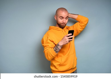 A bearded guy in a yellow sweatshirt, opening his eyes wide and pursing his lips, looks into a smartphone scratching his head
