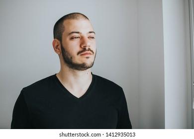 Bearded handosme man behind white backround. Studio photography
