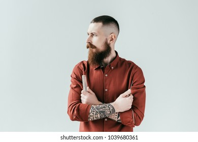 bearded handsome barber holding comb and scissors in crossed arms isolated on white