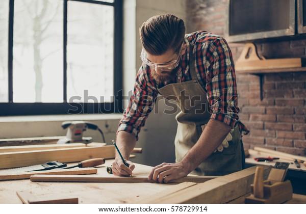 Bärtige, gut aussehende Schreiner auf dem Tisch mit Bleistiftzeichenzeichen auf der Plank.  Stylischer Handwerker mit brutaler Frisur und gesparter Brille arbeitet an seinem Arbeitsplatz.
