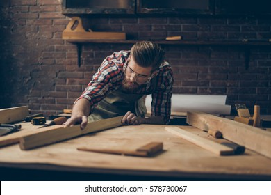 Bearded handsome cabinetmaker at the tabletop with tools.  Stylish craftsman with brutal hairstyle and saved glasses holding woodenplank at his workstation.