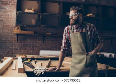 Bearded handsome joiner  think and look to the side near tabletop with tools.  Stylish craftsman with brutal hairstyle and saved glasses holding hands in pocket at his workstation.