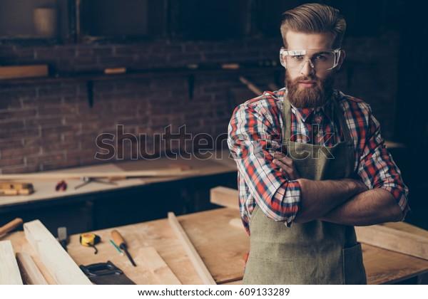 Bärtige gut aussehende Tischler denken und schauen Sie sich Kamera nahe Tischplatte mit Werkzeugen an.  Stilvoller junger Unternehmer mit brutaler Frisur und gesparter Brille überquerte die Hände an seinem Arbeitsplatz.