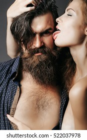 bearded handsome man with bare chest and female slim flexible body of young pretty sexy woman or girl with long blonde hair licking male face