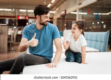 Bearded handsome man with daughter sitting on mattress. Choosing mattress in store. Happy family in store of orthopedic furniture.