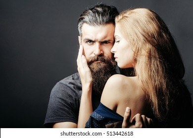 bearded handsome man and female slim flexible body of young pretty sexy woman or girl with bare back has long blonde hair embracing, copy space
