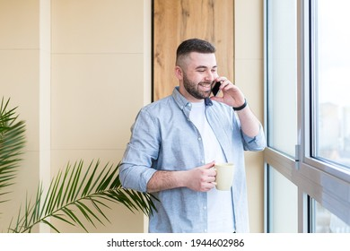 bearded handsome man stands by window with a cup in his hand on the balcony and drinks a hot coffee or tea. male in casual clothes enjoys view through in office or home, relaxing or timeout at work