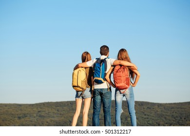 Bearded handsome man and two pretty sexy cute girls or women in jeans and shorts with backpacks outdoor on sunny day with raised hands on blue sky background