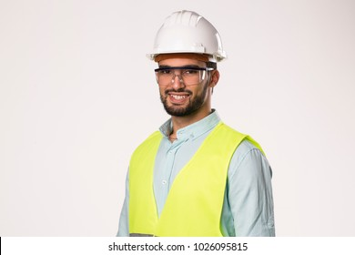bearded handsome smiling engineer worker l , wearing security helmet glasses and vest , isolated on white