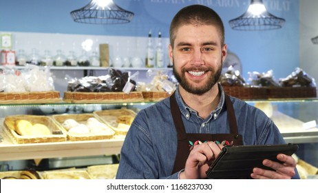 Bearded handsome young male baker working at his shop using digital tablet smiling to the camera online shopping business consumerism profession occupation job e-commerce.