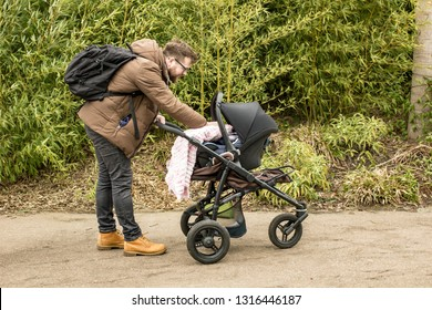 Bearded happy, smiling father with a backpack and in yellow shoes walking with a pram in a spring park shows care and love by covering a small child with a blanket.