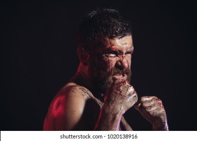 Bearded hipster with blood paint on angry face. Man in fight position with fists on black background. Sport, boxing, fighting. Power, might, magic. Halloween, holidays celebration.