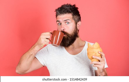 Bearded hipster enjoy breakfast drink coffee. Morning tradition concept. Fresh baked croissant. Delicious breakfast. Man start morning with coffee and croissant. Unhealthy but yummy breakfast.