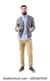 Bearded hipster in gray cardigan vest showing thumbs up with confused expression. Full body length portrait isolated on white studio background.