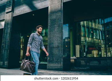 Bearded hipster guy dressed in casual wear holding bag in hand strolling on street in urban setting near big mall.Stylish young man 20 years old walking outdoors and going to sport gym