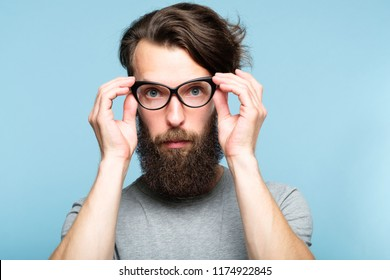 bearded hipster guy fixing his cat eye glasses. stylish modern fashionist. portrait of a geeky quirky eccentric man on blue background.