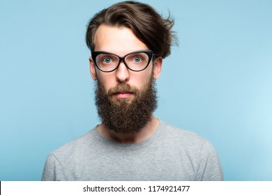 bearded hipster guy wearing cat eye glasses. stylish modern fashionist. portrait of a geeky quirky eccentric man on blue background.