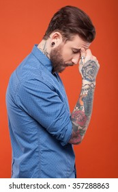 Bearded hipster has a headache. He is standing and touching his forehead with frustration. Isolated on red background