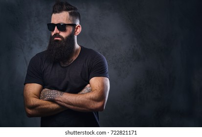 Bearded hipster male with crossed arms, dressed in a black t shirt and sunglasses over grey background.