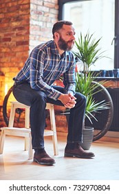 A bearded hipster male dressed in a fleece shirt sits on a wooden chair, near the window in a room with loft interior