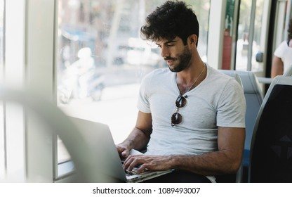 Bearded hipster male is working on a portable computer connected to public wi-fi while sitting in a city train. Young attractive male is looking at the screen while typing messages by a laptop.