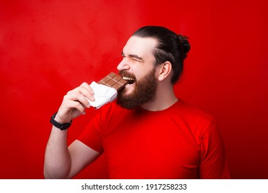 Bearded hipster man eating tasty bar of chocolate over red background.