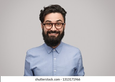 Bearded hipster man in glasses and blue shirt looking cheerfully at camera on gray background