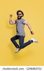 Bearded hipster man in hat and sunglasses jumping and posing on yellow studio background.