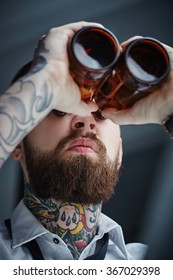 Bearded hipster man holding beer bottles like binocular.