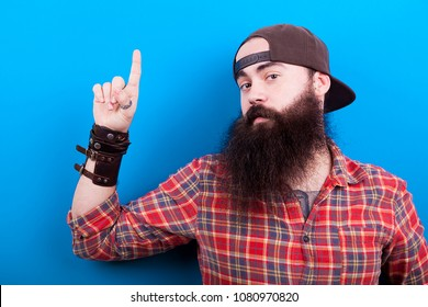 Bearded hipster man with long beard pointing up on blue background