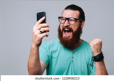 Bearded hipster man looking at phone and celebrating success