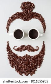 Bearded hipster man made of coffee beans with glasses made of cups of coffee.