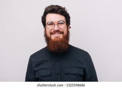 Bearded hipster man in round glasses and black shirt looking cheerfully at camera on gray background