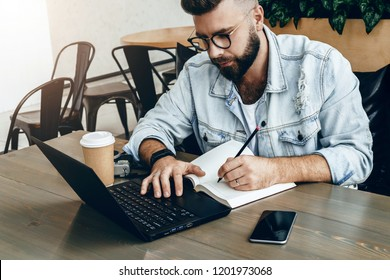 Bearded hipster man sits at table in front of laptop and writes in notebook,student prepares for exams,freelancer works on computer in cafe.Online education for adults, e-marketing, business planning.