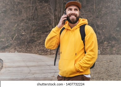 Bearded hipster man tourist in yellow hoodie and cap with backpack stands outdoors, talking on mobile phone. Traveler walks, smiling man calling friends. Telephone conversation. Lifestyle.